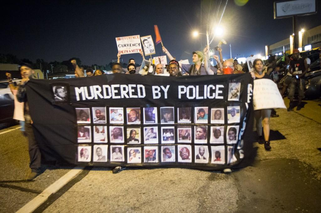 """من الشعارات التي رفعها المحتجون على مقتل الشاب براون في فيرغسون و تقول """"اغتيلوا من قبل الشرطة"""". الصورة من فليكر لراديو الشباب أو Youth Radioمنشورة تحت رخصة المشاع الإبداعي"""